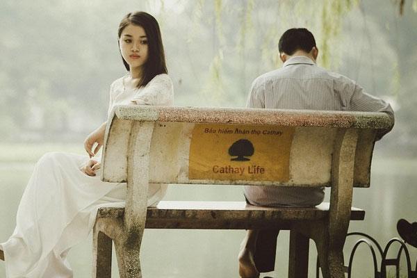 marido e esposa sentados triste no banco da praça