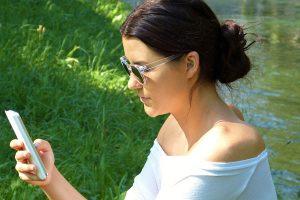 mulher mandando sms na beira do lago