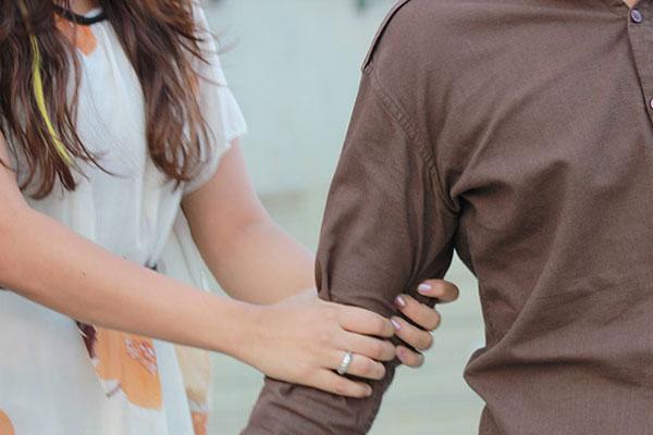 mulher segurando o braço de um homem