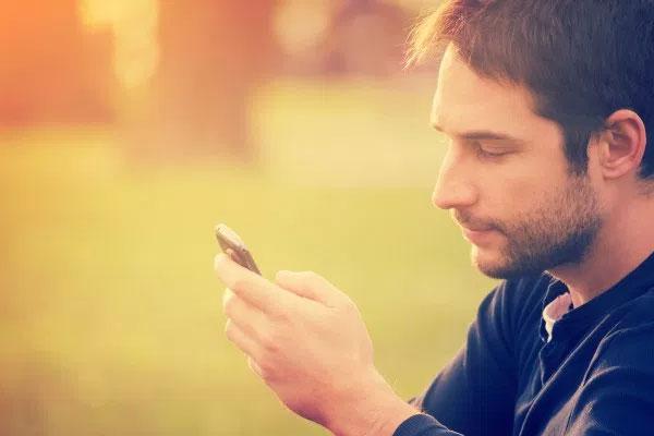 homem olhando sms que recebeu da ex namorada
