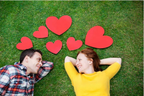 casal apaixonado deitado na grama se tratando bem